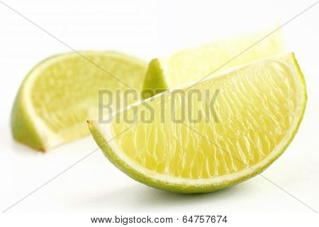 Lime wedges arranged on a white surface. Selective focus.