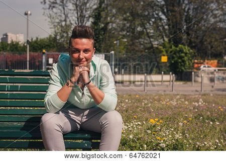 Portrait Of A Short Hair Girl Sitting On Bench