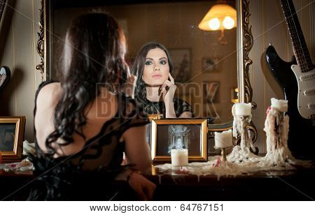 Beautiful woman in black lace dress in vintage scenery with candles. Portrait of brunette