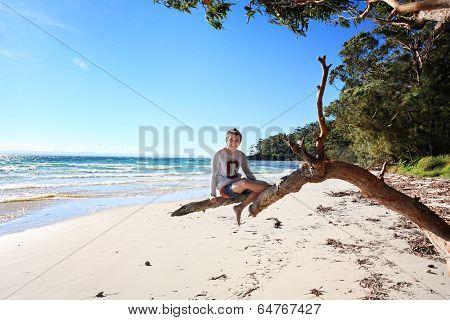 Cheerful Teen Boy Sitting On Tree  Holiday At The Beach Australia