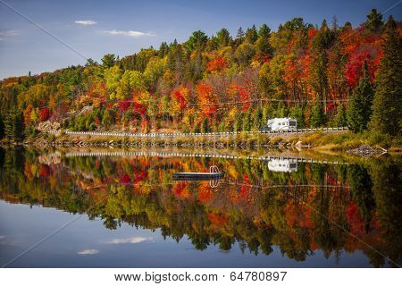 Fall forest with colorful autumn leaves and highway 60 reflecting in Lake of Two Rivers.  Algonquin Park, Ontario, Canada.