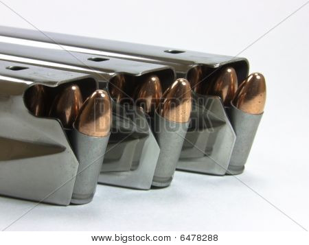 3 magazines loaded with 9mm ammo on white background - 2