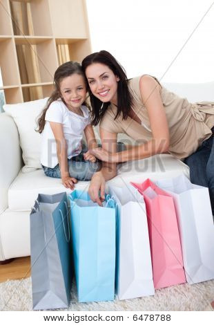 Smiling Mother And Her Daughter Opening Shopping Bags