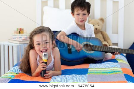 Little Boy Playing Guitar And His Sister Singing