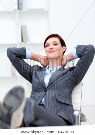 Businesswoman Sitting In Office With Feet On Desk Relaxing