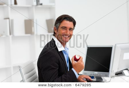 Businessman Eating A Fruit At Work