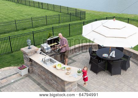 Father And Daughter Preparing A Barbecue
