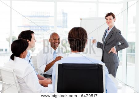 Confident Businesswoman Giving A Presentation To Her Team