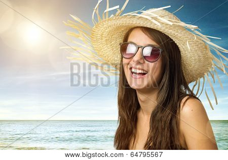 Pretty young girl smiling with straw hat and sun glasses in the beach