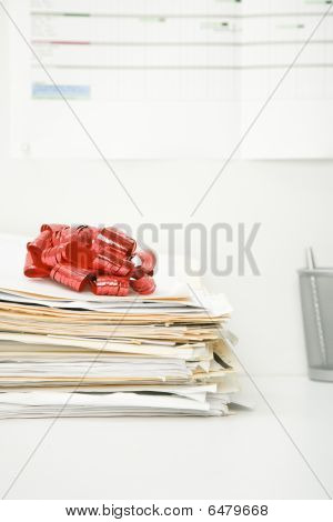 Stack Of Files Topped By A Gift Bow