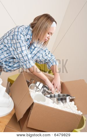 Moving House: Woman Unpacking Box With Pot