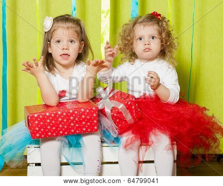 Little girls in fluffy skirts with gift boxes
