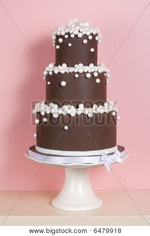 Three-tiered Chocolate Cake Against Pink Background