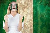 picture of nigeria  - Excited nigeria fan in face paint cheering against nigeria flag in grunge effect - JPG