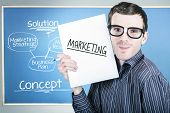 picture of dork  - Humorous portrait of an education marketing man wearing dork glasses displaying business plan for strategy success - JPG