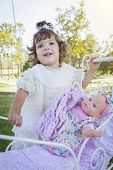 image of baby doll  - Adorable Young Baby Girl Playing with Her Baby Doll and Carriage Outdoors - JPG