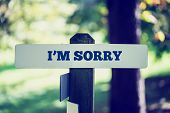 stock photo of apologize  - Vintage faded effect image of a rustic wooden signpost in woodland with words  - JPG