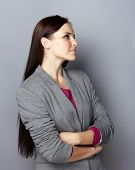 pic of blazer  - Portrait of a young smiling business woman with long brunette hair on gray studio background - JPG