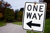 stock photo of road sign  - One way sign pointing towards a winding road leading into bushes - JPG