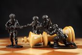 stock photo of killing  - Toy soldiers killed chess king on chessboard.