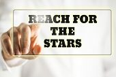 stock photo of reach the stars  - Phrase Reach for the stars on a virtual interface in a navigation bar with male finger touching it from behind - JPG
