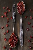 stock photo of barberry  - Spice barberry in spoons on wooden background - JPG