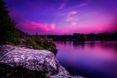 stock photo of shoreline  - A violet sunset over a calm lake with trees on a rocky shoreline - JPG