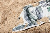stock photo of 100 dollars dollar bill american paper money cash stack  - 100 dollar bill buried in the sand - JPG