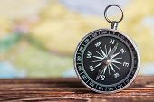 stock photo of cartographer  - compass on the table against the background of a tourist card - JPG