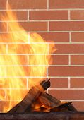 picture of brazier  - burning wood in a brazier on the brick wall background - JPG