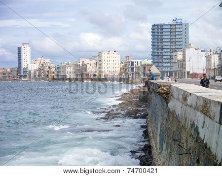 HAVANA,CUBA - OCTOBER 24, 2014 : View of the Havana skyline with people walking and fishing near the ocean