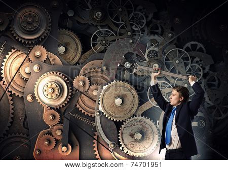 Young businessman fixing gears mechanism with wrench