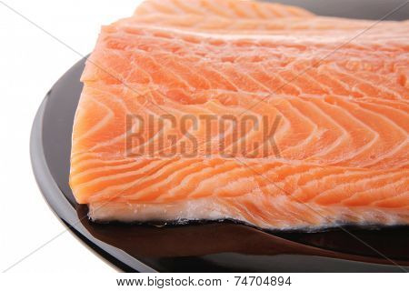 fresh uncooked red fish fillet on black over white