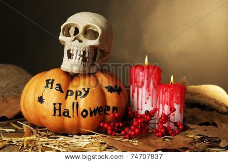 Halloween pumpkin  and bloody candles on wooden table on dark color background