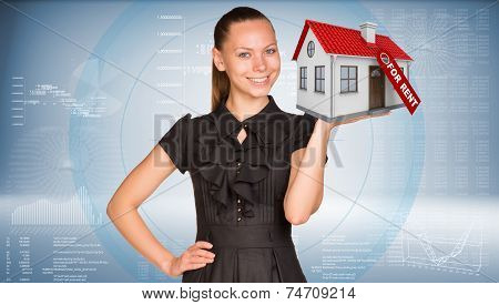 Businesswoman smiling and holding house in hand