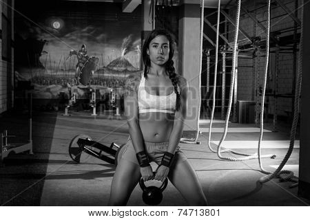 brunette girl kettlebell swing weightlifting workout exercise at gym