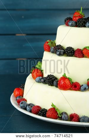Beautiful wedding cake with berries on  dark wooden background