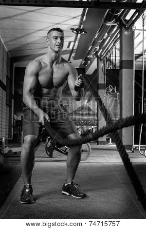 battling ropes man at gym workout exercise fitted body