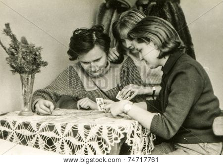 POLAND, CIRCA FIFTIES: Tree young women play solitaire, vintage photo