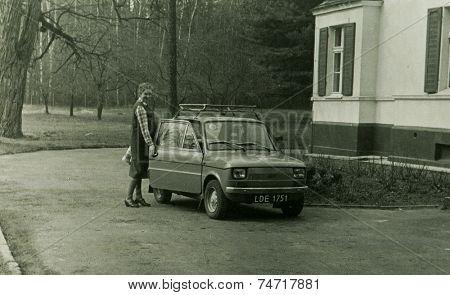 POLAND, CIRCA 1981: Young pregnant woman enters Fiat 125p car, produced in Poland, vintage photo