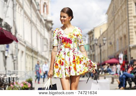 Beautiful young woman in sexy dress, against of summer street
