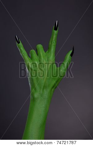 Green monster hand with black nails showing heavy metal gesture, studio shot on black background