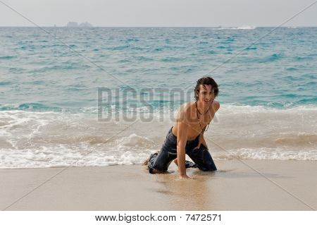 Athletic young man coming out of the ocean.