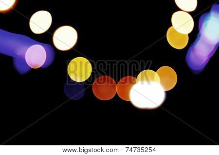 Defocused carlights over dark background. Urban bokeh background. Defocused spots of light
