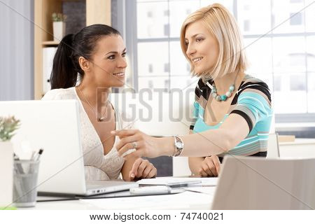 Casual brunette and blonde caucasian happy female office workers having a meeting in front of laptop computer