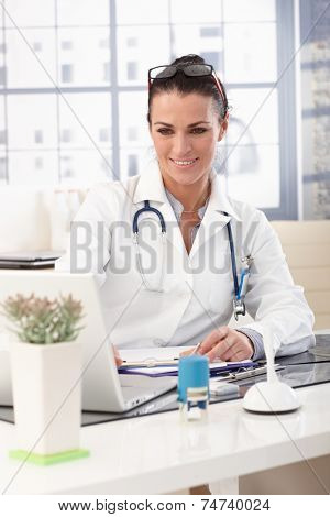 Closeup of happy brunette doctor working on laptop computer at medical office, wearing glasses, stethoscope and lab coat, smiling.
