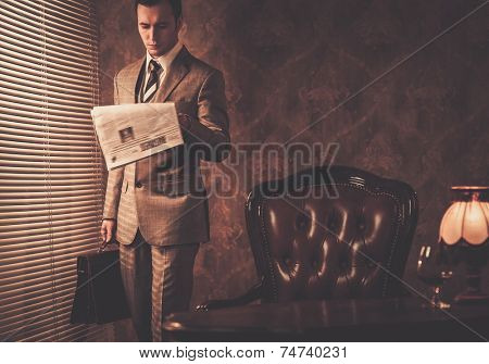 Well-dressed businessman reading newspaper