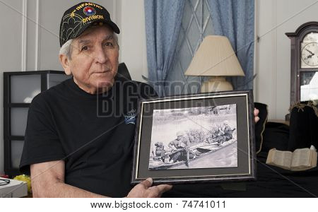 Vietnam War Veteran Holds An Old War Photo Of Himself.