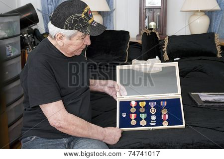 Vietnam Vet Looks Over His Medals