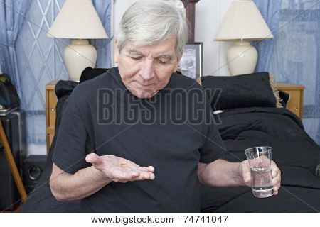 Senior Taking Medication With Water